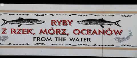 Informationstafel am Eingang eines Restaurants mit Darstellungen von Fischen