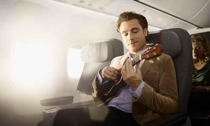 Ein Mann spielt in einem Flugzeug Gitarre.