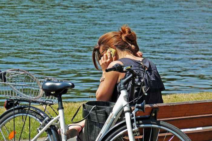 Telefonierende Frau auf einer Bank am See