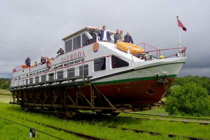Ein Schiff wird auf Schienen am Oberlandkanal über Land gezogen.