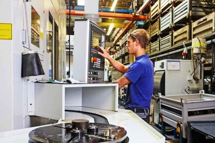 Ein Facharbeiter kontrolliert an einem Display eine programmierbare Maschine