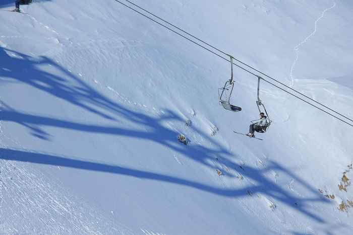 Wintersportler fahren mit einem Skilift einen Berg hinauf