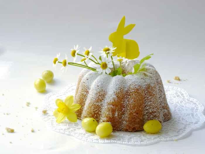 Mit Kamillenblüten, einer Narzisse und einem Osterhasen garnierter Topfkuchen