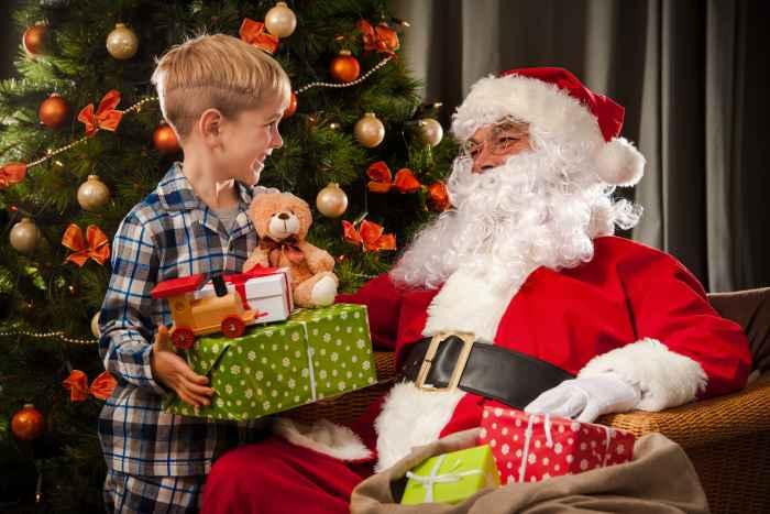 Weihnachtsmann und Junge vor einem Weihnachtsbaum