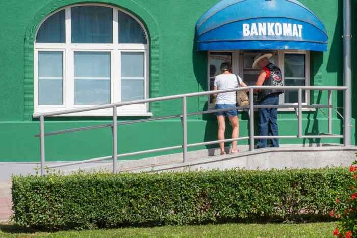 Bankkunden heben Geld an einem Geldautomaten in Polen ab