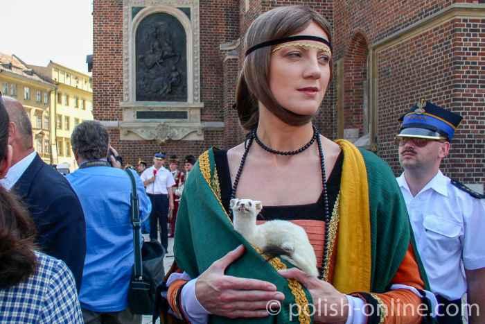 Eine als Dame mit dem Hermelin verkleidete Frau neben der Marienkirche in Krakau (Kraków)