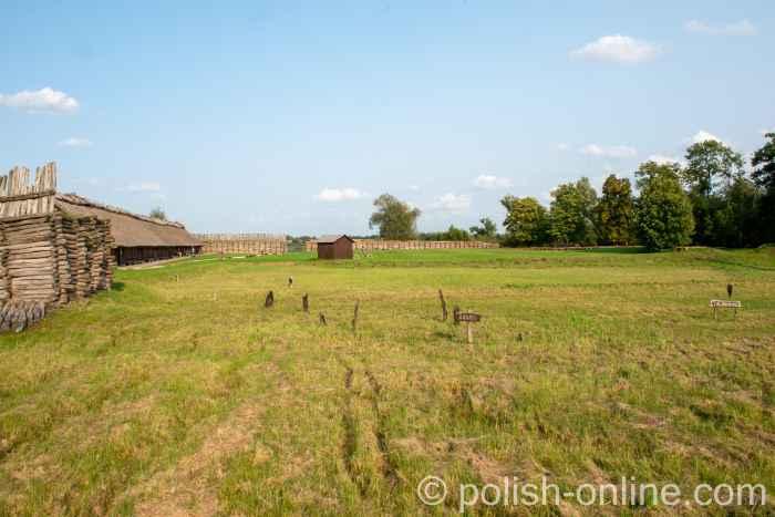 Pfähle ragen neben einer rekonstruierten Lausitzer Niederburg in Biskupin aus der Erde