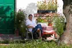 Frau vor ihrem Haus in Cadinen (Kadyny)
