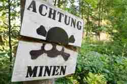 Schild im Mauerwald, das vor Minen warnt