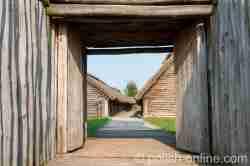 Blick durch das Tor der Niederburg in Biskupin auf die Langhäuser