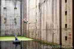 Ein junger Mann schwingt an einem Seil in der Schleusenkammer der Oberschleuse bei Fürstenau (Leśniewo)