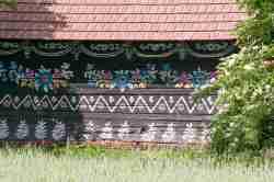 Braun getünchtes und mit Blumen bemaltes Holzhaus in Zalipie