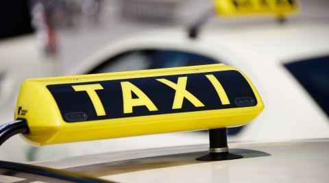 Taxischild auf einem gelben Taxi