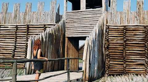 Eine Frau steht vor dem Zugang zur restaurierten Niederburg in Biskupin in Polen