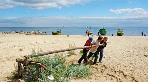 Fischer ziehen in Orlowo ein Boot an Land.