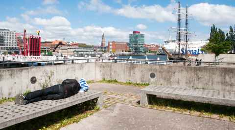 Ein Obdachloser schläft auf einer Bank an der Kieler Förde