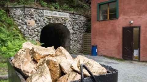 Lore, die mit goldfarbenen Steinen gefüllt ist, vor dem Eingang eines Stollens in Reichenstein (Złoty Stok)