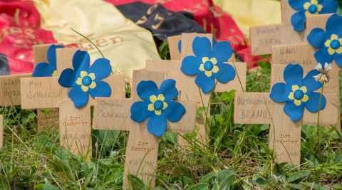 Kleine mit Blumen geschmückte Holzkreuze auf dem Soldatenfriedhof Bartossen in Masuren